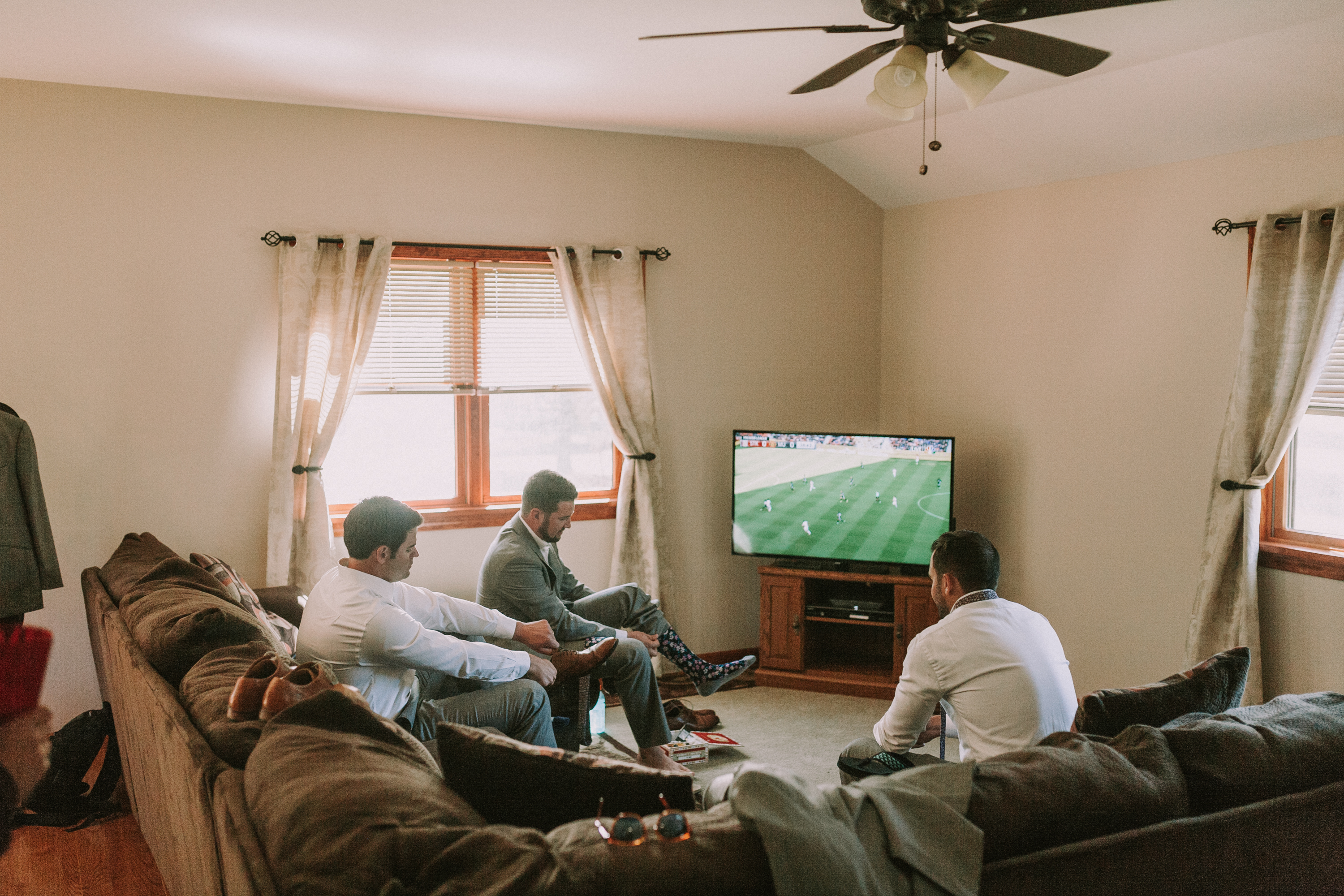 groomsmen watching the game, groomsmen hanging out, groomsmen watching soccer, groomsmen putting on shoes