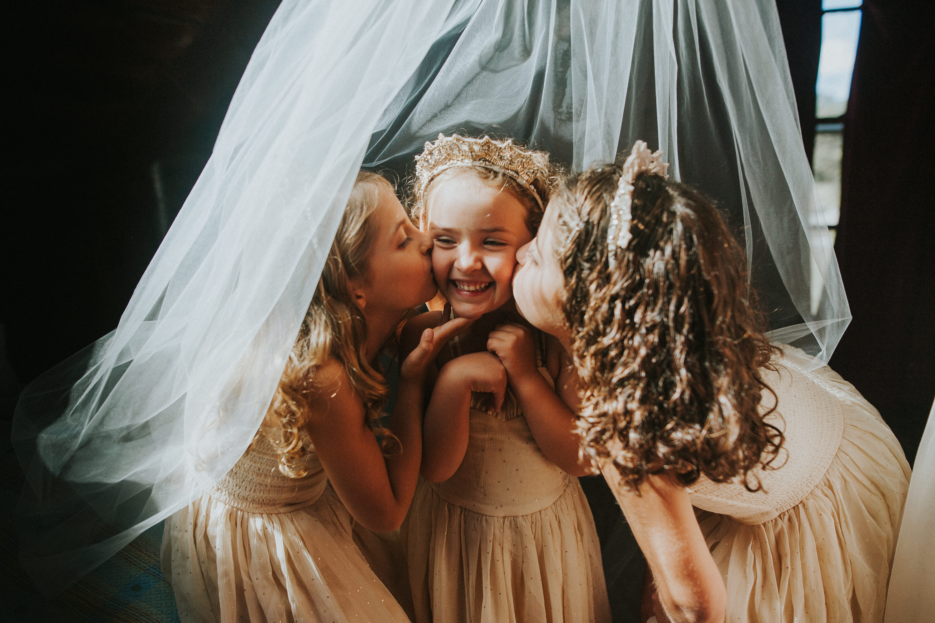flower girls under veil, flower girl sisters, flower girl kiss