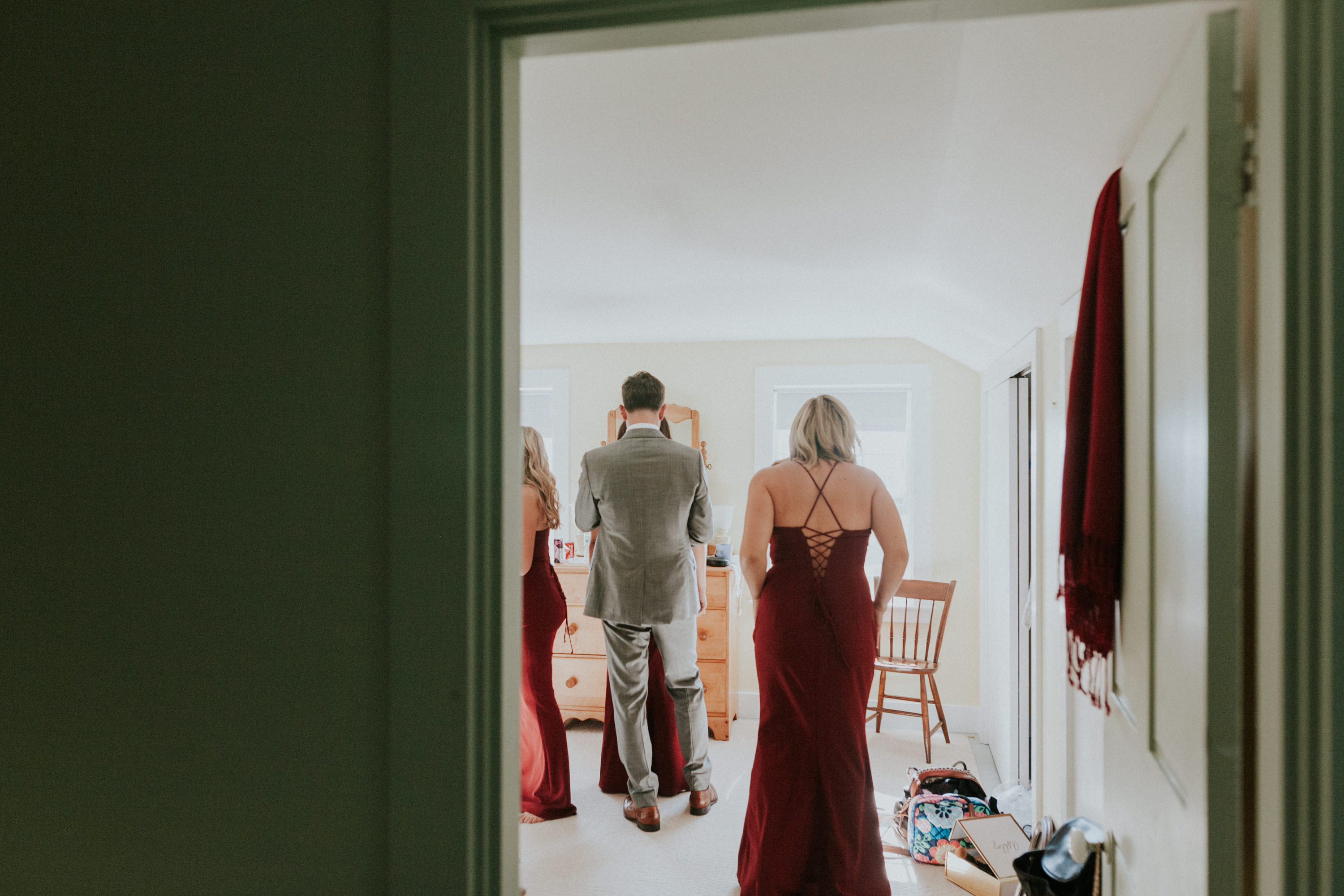 bridesmaid putting on dress, bridesmaids helping eachother
