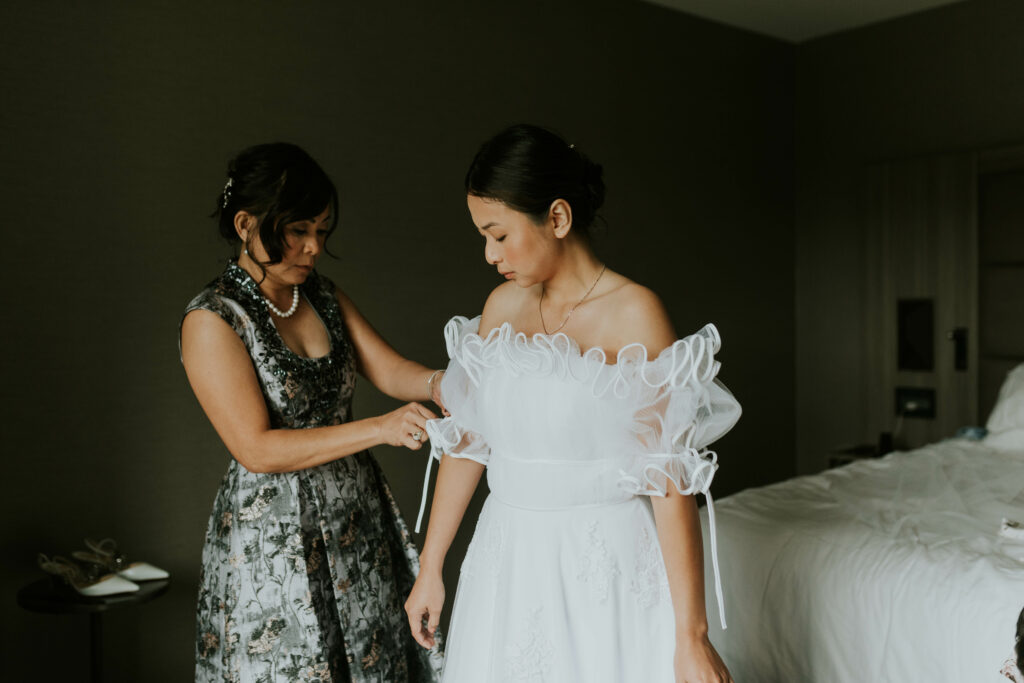 mother of the bride doing up wedding dress