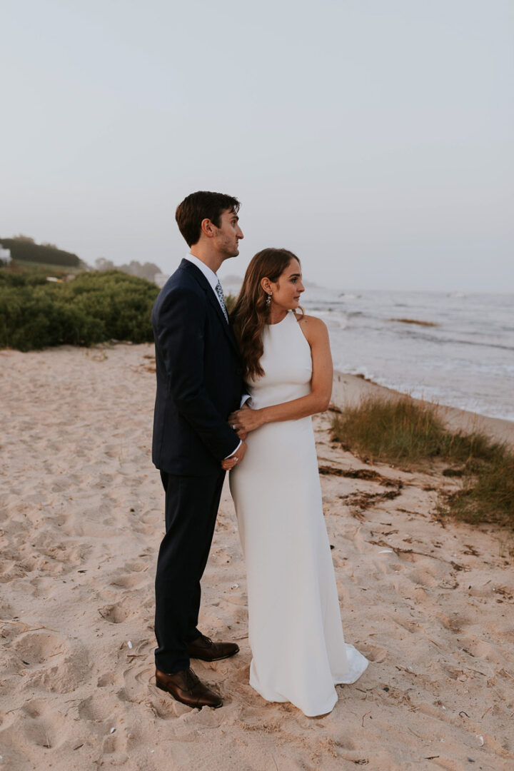 Cape Cod bride and groom stand on the beach looking out at the ocean